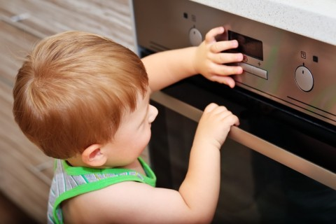 dziecko-bawi-sie-przy-kuchence-elektrycznej